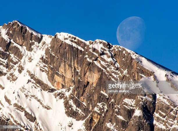 The moon sets behind Watzmann peak above the town of Schönau am KoenigsseeGermany 15 February 2017 Photo Peter Kneffel/dpa   usage worldwide