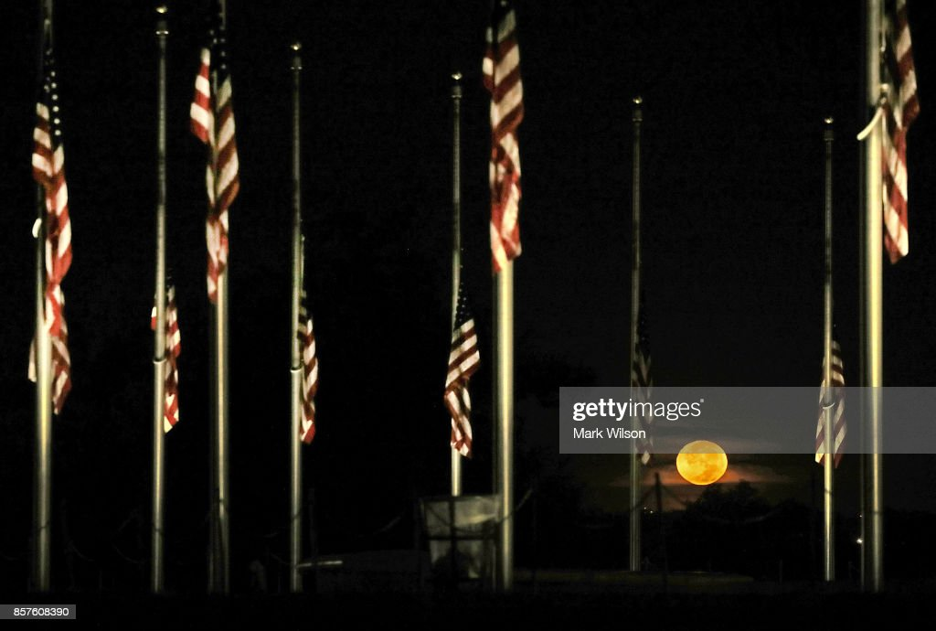 The moon sets beyond the American flags on the grounds of the Washington Monument have been lowered to half-staff, on October 4, 2017 in Washington, DC. President Donald Trump ordered the flags on all federal buildings to fly at half-staff following the mass shooting that left more than 50 dead in Las Vegas. The gunman, identified as Stephen Paddock, 64, of Mesquite, Nevada, opened fire from the Mandalay Bay Resort and Casino on an outdoor music festival. The investigation is ongoing.