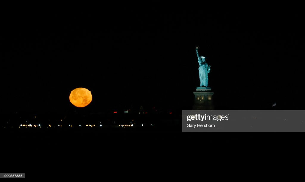 The moon sets next to the Statue of Liberty before sunrise on January 1, 2018 in New York City.