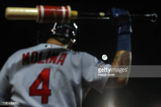 The moon shines behind Yadier Molina of the St Louis Cardinals as he stands on deck in the sixth inning against the Washington Nationals during game...