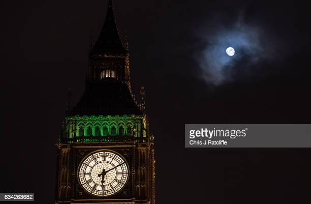 The moon shines through a brief break in the clouds behind Elizabeth Tower commonly known as Big Ben as the Ayrton light is on above the belfry...