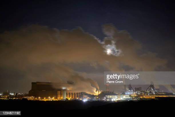 The moon shines through fumes of the Tata Steel plant on August 20, 2021 in Wijk aan Zee, Netherlands. The Tata steel plant is under investigation by...