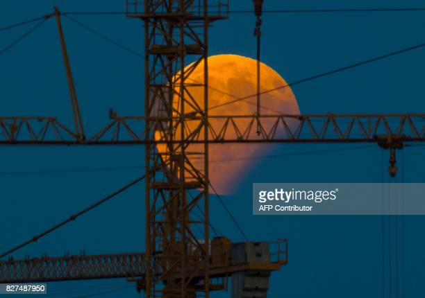 TOPSHOT The moon standing in a partial lunar eclipse can be seen behind a constructin crane on August 7 2017 in Gilching southern Germany / AFP PHOTO...