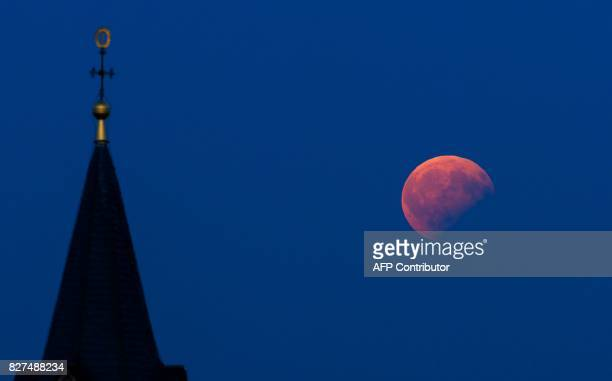 The moon standing in a partial lunar eclipse hangs in the sky over Bad Staffelstein southern Germany on August 7 2017 / AFP PHOTO / dpa / Nicolas...