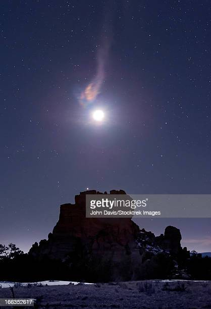 the moonlight creates a rainbow effect through a wispy cloud that hangs over a rock formation in the el malpias national monument, new mexico. - moonbow ストックフォトと画像