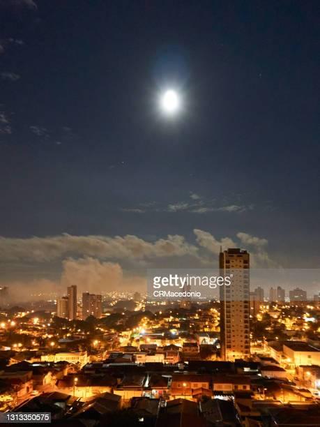 the moon's glow over the city. - crmacedonio fotografías e imágenes de stock