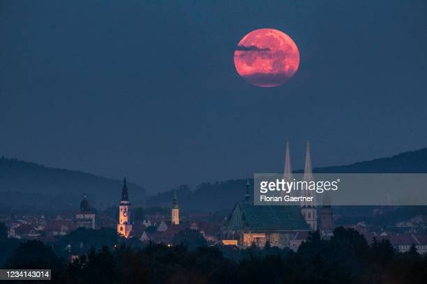 The moonset is seen behind the old city of Goerlitz, border city to Poland, on July 24, 2021 in Zgorzelec, Poland.