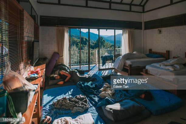 the morning after chinese male hang over oversleeping in bedroom with messy blankets - after party stock pictures, royalty-free photos & images