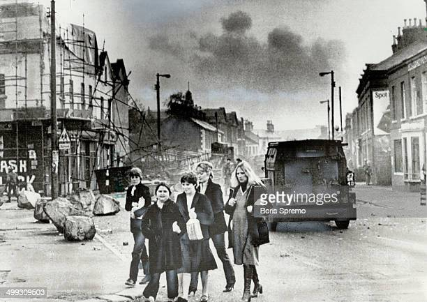 The morning after Women walk to work past the rubble left after a night of rioting in the predominantly Catholic Falls Road area of Belfast The riots...