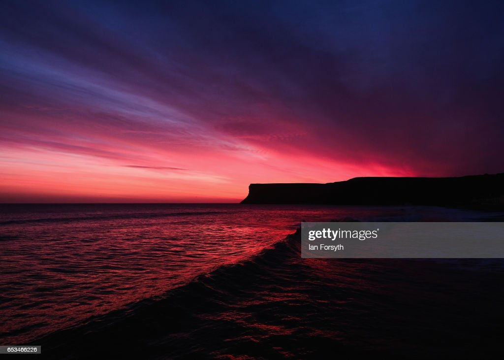 The morning sky lights up in a dramatic red as the sun begins to rise behind Huntcliff on March 15, 2017 in Saltburn-by-the-Sea, England. Fine conditions are expected to remain for much of the day in many parts of the country.