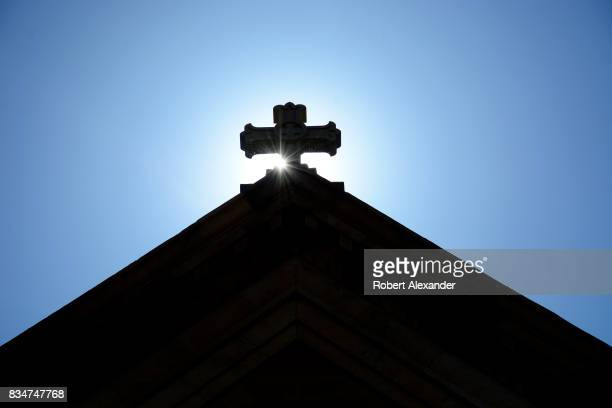 The morning sun rises behind a stone cross atop The Cathedral Basilica of St Francis of Assisi commonly known as Saint Francis Cathedral in Santa Fe...