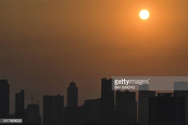 The morning sun rises past buildings and haze over the Jakarta city skyline on August 17 2018 Indonesia is about to open the Asian Games but its...