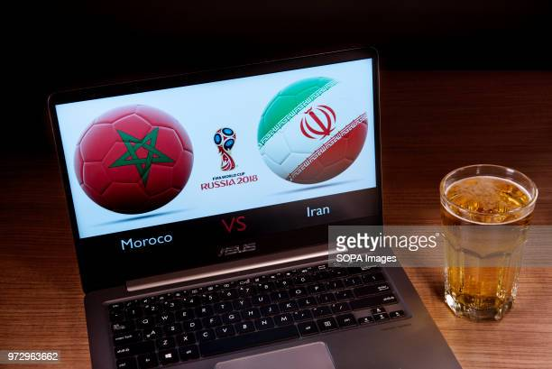 The Moroccan and Iranian flags seen together with the Russian 2018 World cup logo displayed on a laptop next to a glass of beer This game belongs to...