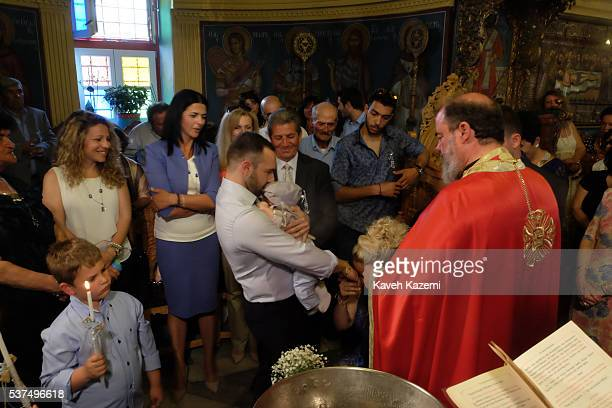 The mother of a baby boy kneels and kisses her husband's hand while the father holds the baby in his arms during his Christening ceremony attended by...