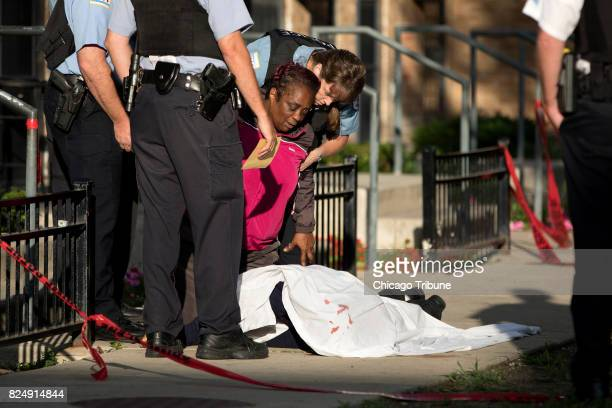 The mother of a gunshot victim kneels over his body at the scene of a fatal shooting in the 500 block of West Iowa Street on Friday July 28 in the...