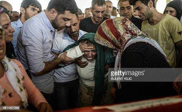 The mother of a victim cries for her son near his coffin during a funeral ceremony in Gaziantep on July 21 following a suicide bomb attack the day...