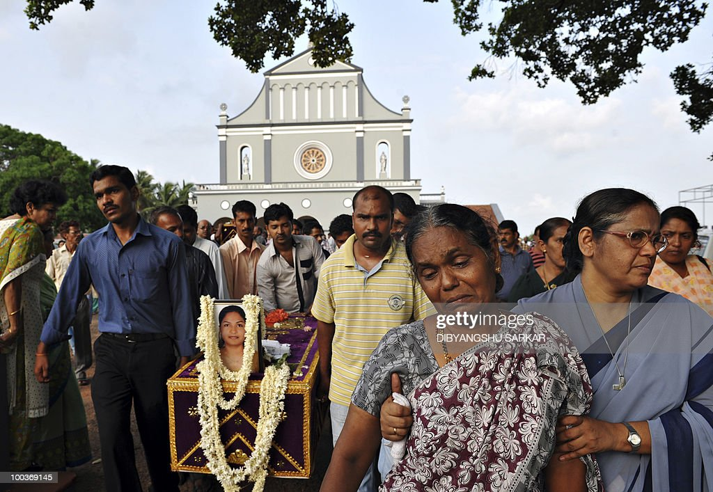 The mother of Air India Express crash victim Savitha Philomene D'Souza (2nd R) mourns as relatives carry her coffin for burial at the Holy Cross Church in Mangalore on May 24, 2010. Investigators on May 22 widened the search for the 'black box' data recorder of an Air India Express that crashed into a gorge killing 158 people, as the airline denied lax safety claims. AFP PHOTO/Dibyangshu SARKAR