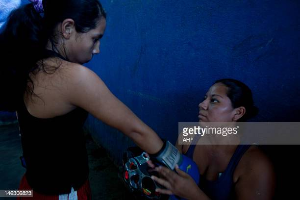 The mother of an amateur female boxer adjusts her daughter's glove in Managua on June 11 2012 AFP PHOTO / Nicolas GARCIA