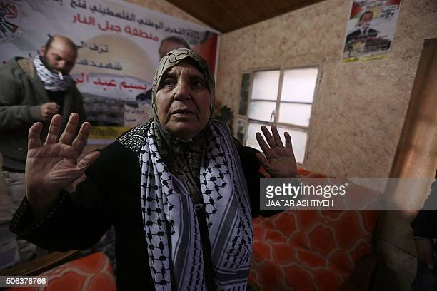 The mother of Bassim Salah sits next to a portrait of her son who was killed on November 29 after allegedly attempting to stab an Israeli border...