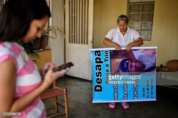 The mother of Geovanny Lopez, who disappeared in a shipwreck en route from Venezuela to Trinidad and Tobago on May 16 holds a poster with a picture...