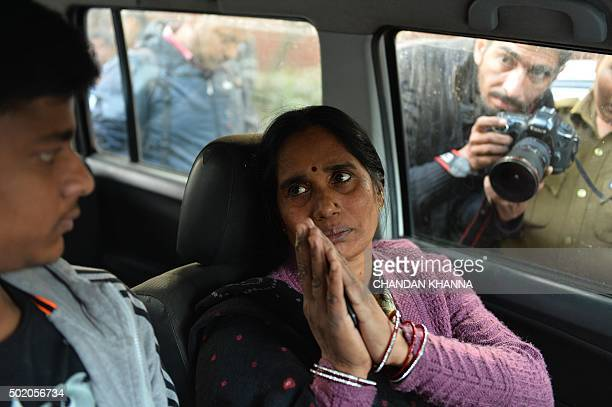 The mother of Indian gangrape victim 'Nirbhaya' gestures as she sits in a vehicle as she heads to a rally in New Delhi on December 20 held to protest...