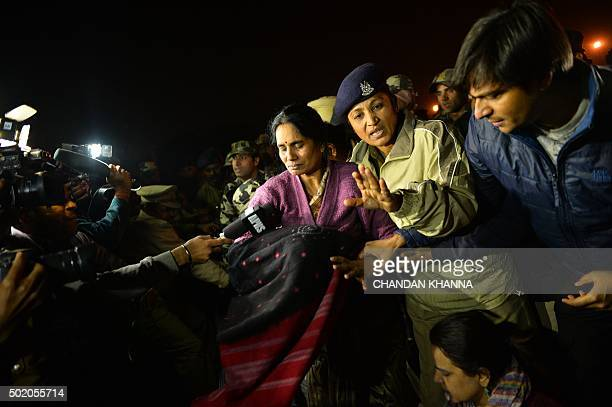 The mother of Indian gangrape victim 'Nirbhaya' is detained by police officials as she attends a rally in New Delhi on December 20 held to protest...