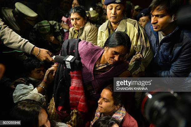 The mother of Indian gangrape victim 'Nirbhaya' is shielded by demonstrators as police officials prepare to detain her as she attends a rally in New...