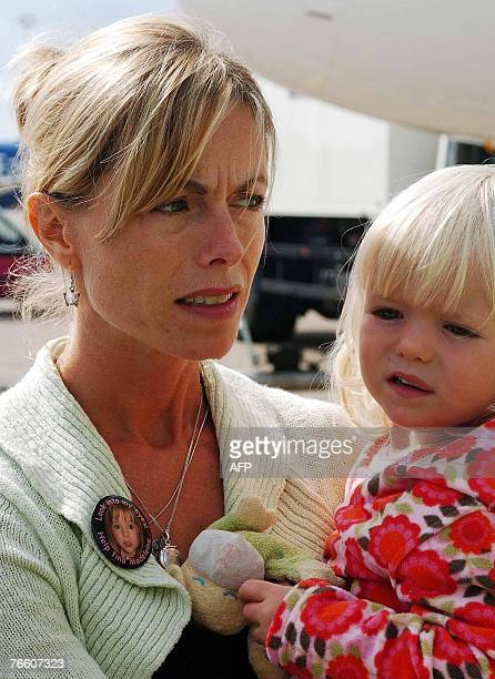 The mother of missing toddler Madeleine McCann Kate carries her twoyearold twin daughter Amelie as she and her husband Gerry arrive back in Britain...