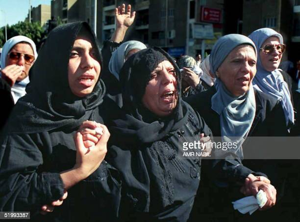 The mother of one of the victims of the 19 November attack on Egypt's embassy in Pakistan weeps as she is supported by her family 21 November in...
