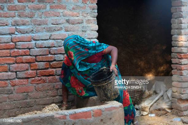 The mother of the 19-year-old woman, who was allegedly gang-raped by four men, does household chores at Bool Garhi village in Hathras in the Indian...