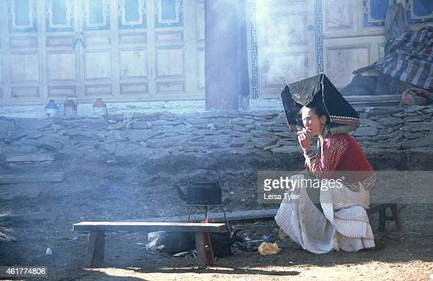 The mother of the bride smoking at her daughter's wedding in a small village in the mountains above Weixi in Yunnan province China The marriage of...