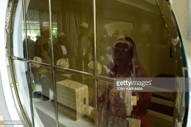 The mother of the bride watches from behind a window as kin and representatives of the groom arrive at the bride's home during a traditional wedding...