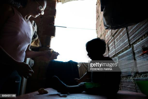 The mother of Venezuelan Rebeca Leon who scavanges for food in the streets of Caracas feeds her grandson at their house in Petare shantytown on...