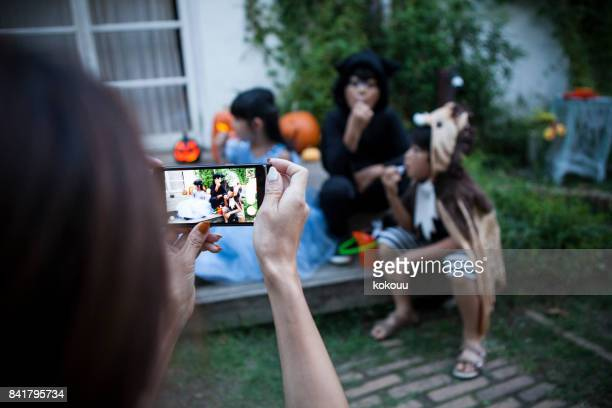 the mother takes pictures of the children. - naughty halloween stock photos and pictures