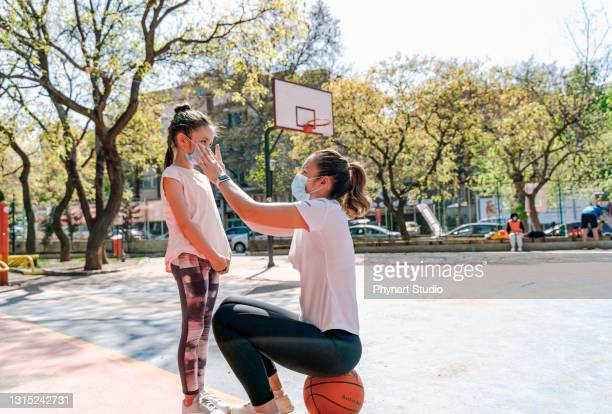 the mother wearing a mask on her daughter after the basketball game - friendly match stock pictures, royalty-free photos & images