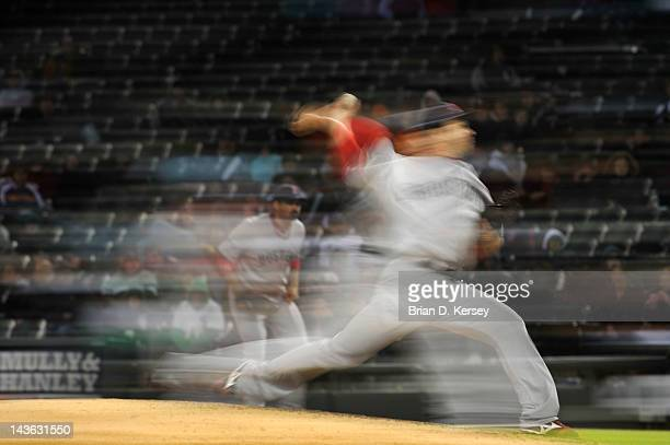 The motion of relief pitcher Junichi Tazawa of the Boston Red Sox is captured with a slow shutter speed on the camera against the Chicago White Sox...