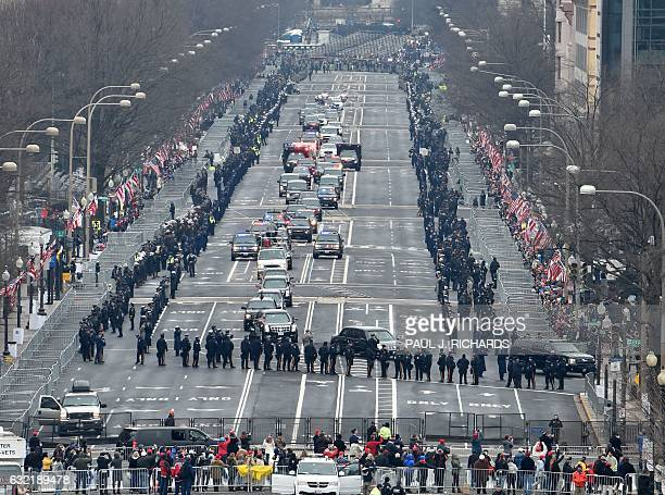 TOPSHOT The motorcade carring US President Barack Obama and Presidentelect Donald Trump roll up Pennsylvania Avenue to the US Capitol in Washington...