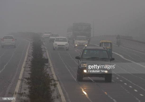 The motorists use lights while going to their destination in the cold and foggy weather near Akshardham on December 28 2012 in New Delhi India While...