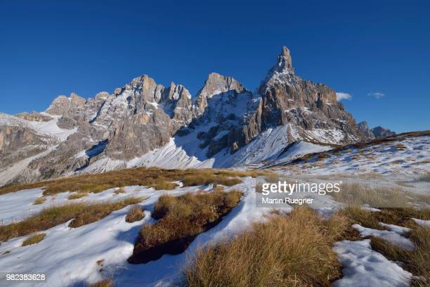 the mountain group pale di san martino with the mountain peak cimon della pala in autumn with first snow. unesco world heritage site. - graspflanze stock-fotos und bilder