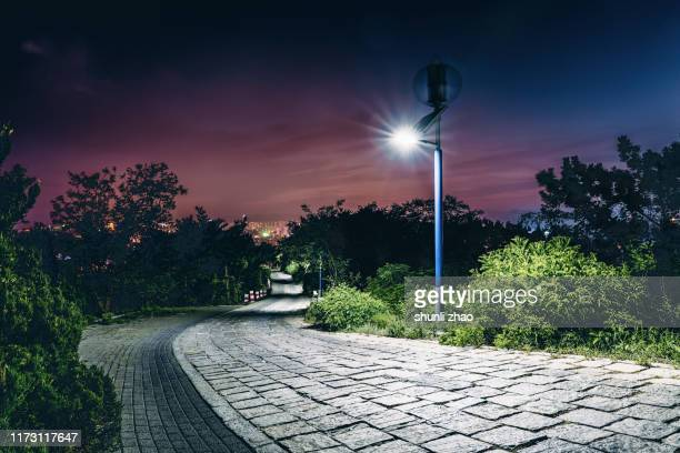 the mountain path at night - street light stock pictures, royalty-free photos & images