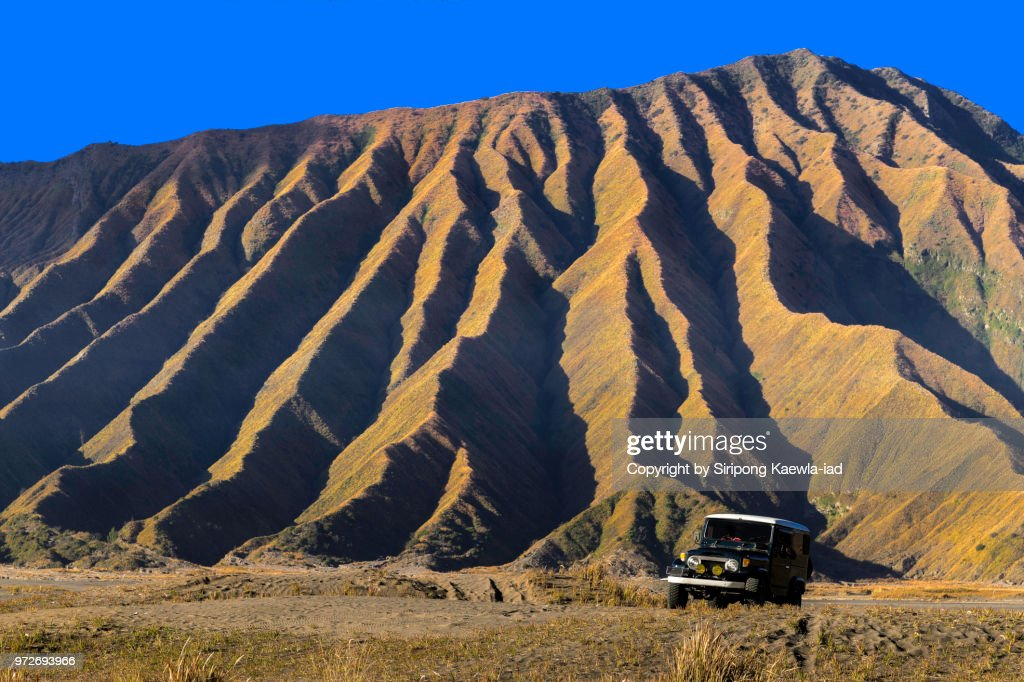 The mountain ridge line of Mt.Bromo volcano with a car in foreground, East Java, Indonesia. : Stock Photo