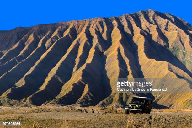 The mountain ridge line of Mt.Bromo volcano with a car in foreground, East Java, Indonesia.