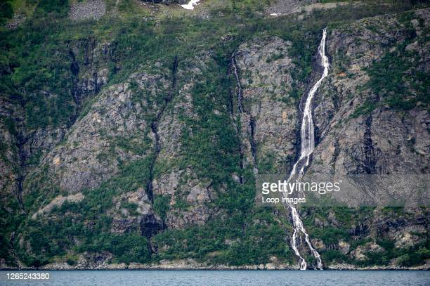 The mountains and waterfalls of the Lyngen Alps meet the sea on Lyngenfjord north of the Arctic Circle in Norway.