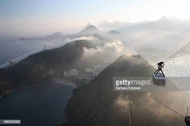 CONTENT] The mountains of Rio de Janeiro fade into the distance Clouds hang low between the mountains in the soft light of sunset A cable car...