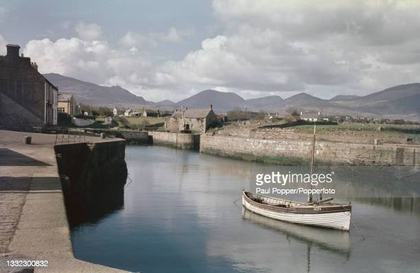 The Mourne Mountains rise up behind a fishing boat moored in the harbour of the seaside village of Annalong in County Down, Northern Ireland circa...