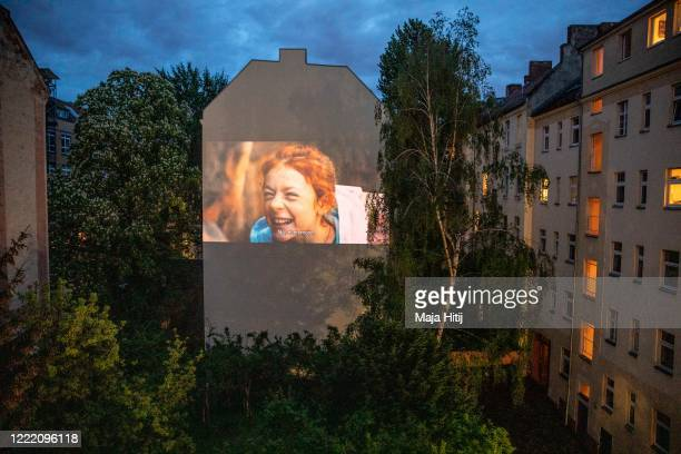 The movie is projected from the home on the backyard firewall of residential building on April 30 2020 in Berlin Germany The project Windowflicks is...