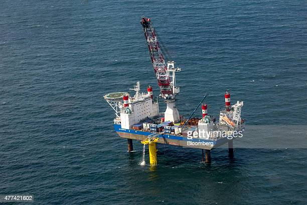 The MPI Enterprise offshore supply vessel stands on support legs beside a wind turbine foundation in the North Sea as installation and construction...