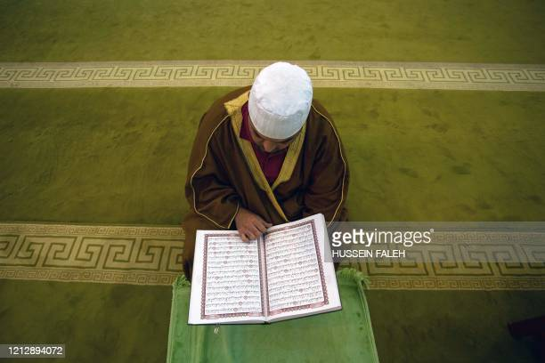 The muazzin of the grand mosque of Basra closed down due to the coronavirus pandemic reads the Koran during the Muslim holy month of Ramadan in the...