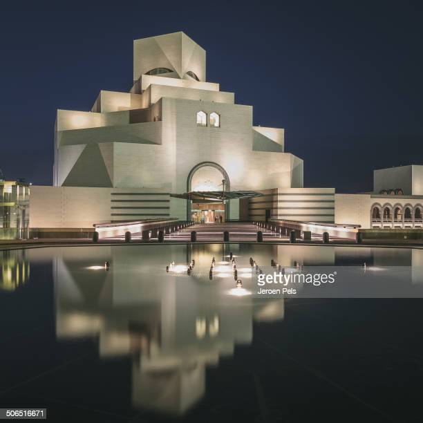 CONTENT] The Museum of Islamic Art in Doha Qatar at night with reflections in the water