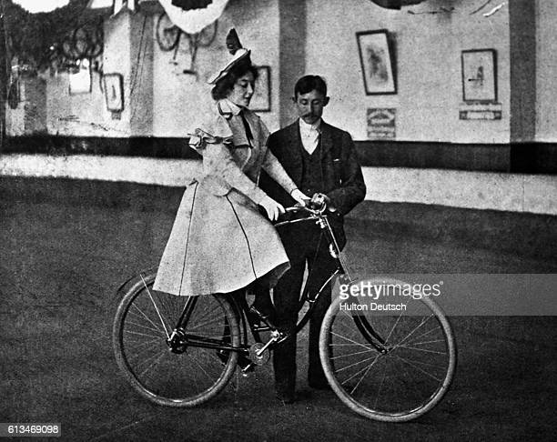 The music hall star Anna Held receives instruction in how to ride a bicycle